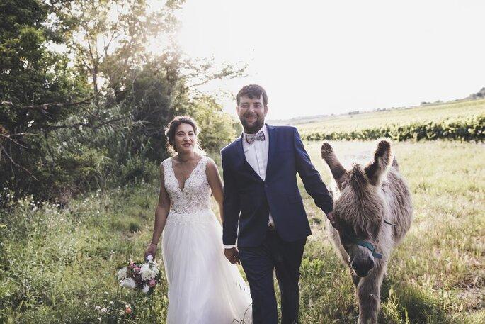 Ma Petite Cérémonie - Deux mariés se tenant par la main et promenant un poney dans un champ