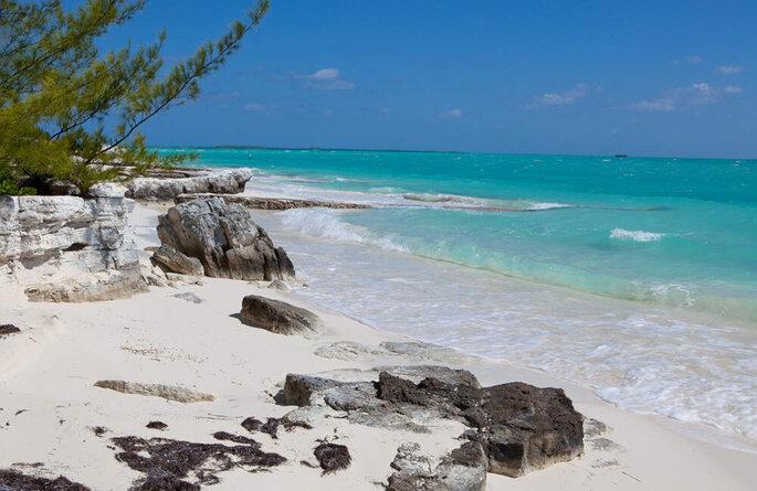 So Traveling agence de voyage, plage de roches et sable blanc bordée de végétation, eaux turquoise