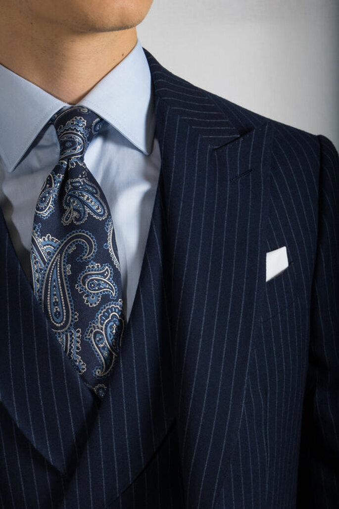 Un homme porte un costume bleu marine a fines rayures. Sa cravate est bleue avec des motifs plus clairs.