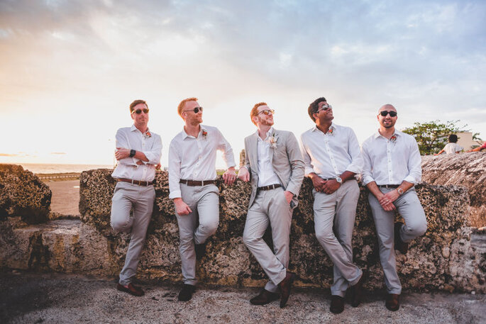 Novio y amigos con trajes beige en lino, recostados en un muro