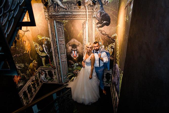 Ein Brautpaar steht in einem farbenfrohen, historischen Treppenhaus, die Location ist das Hotel K7.