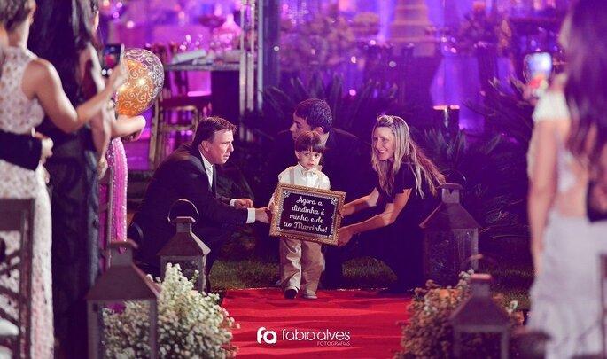 Cerimonialista auxilia o pequeno pajem na entrada da cerimônia