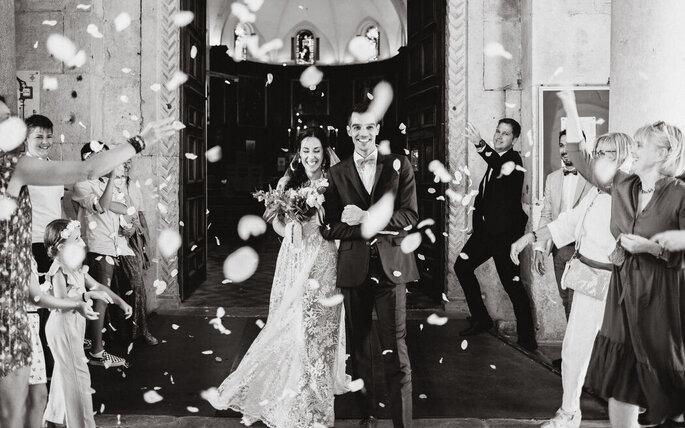 Photo en noir et blanc de deux mariés heureux sortant de l'église avec lancer de pétales