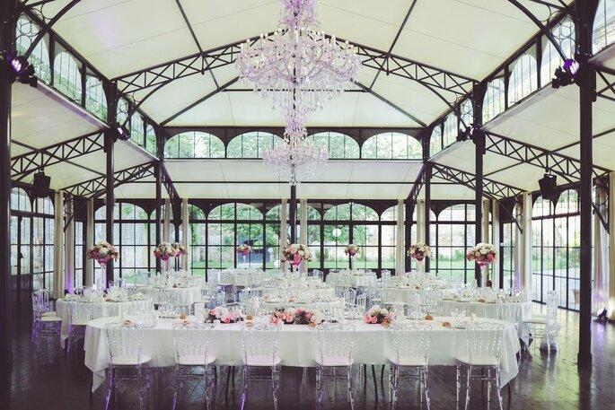 L'Orangerie du Domaine de Montchevreuil décorée pour un mariage avec de grands lustres et des chaises transparentes ainsi que des fleurs