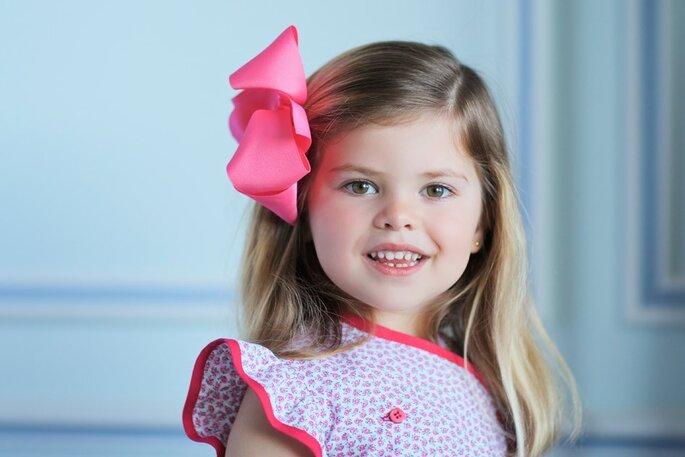 menina com grande laço rosa no cabelo vestido festa casamento
