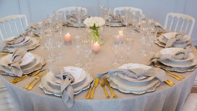 Une table décorée pour un mariage dans les tons beige, avec des bougies et des couverts dorés