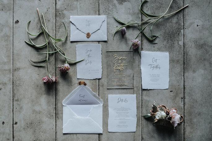 Verschiedene Elemente der Hochzeitspapeterie von Bonjour Paper mit Menü, Einladung und Save the Date-Karte, organisiert von Freakin' Fine Weddings.