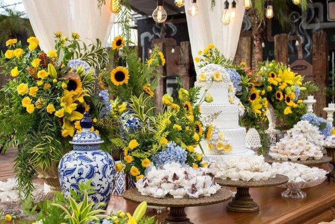 Mesa de doces e bolo com decoração floral amarela