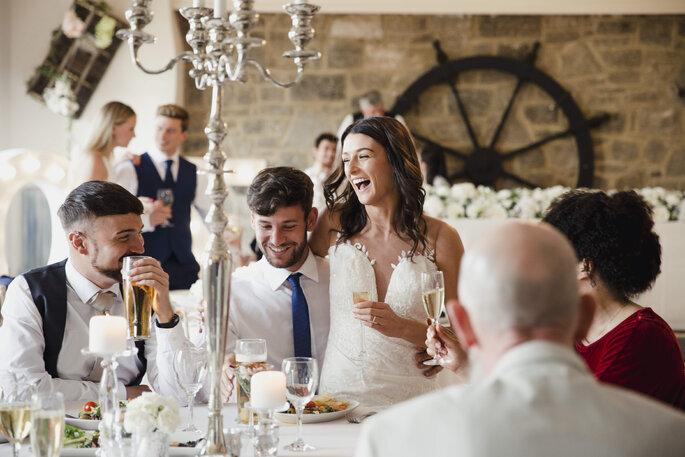 Des mariés et leurs invités rient, assis aux tables de mariage