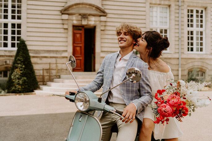 Un couple sur un scooter vintage en tenue de mariés.