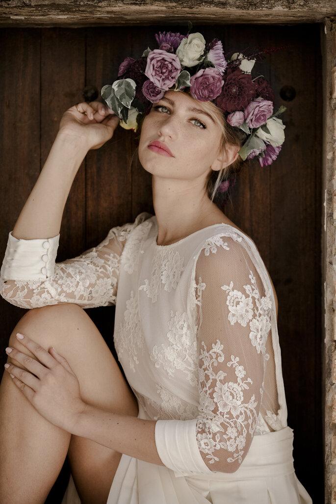 Une mariée portant une robe à manche trois quarts en dentelle transparente avec une couronne de fleurs violettes