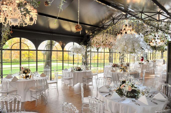 Salle décorée pour une réception de mariage avec des chaises transparentes et des tables blanche paré de bouquets de fleurs