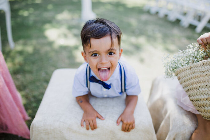 menino com laço e suspensórios num casamento a deitar a lingua de fora