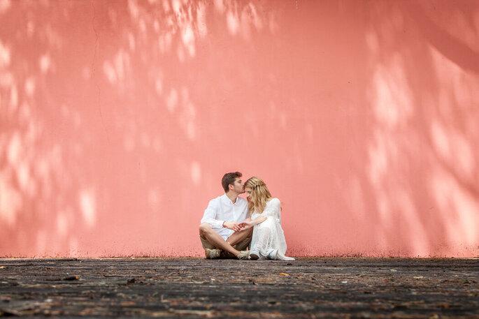 casal sentado no chão parede rosa