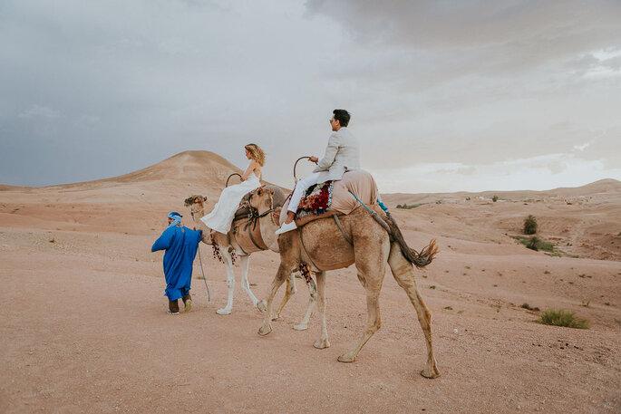 Deux mariés photographiés au Maroc, dans le désert, sur des chameaux - cliché de mariage original