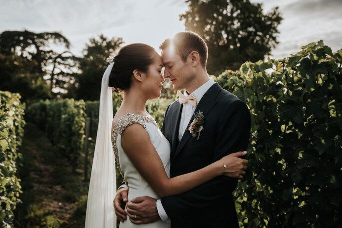Deux mariés pendant la séance photo de couple, dans un cadre romantique et verdoyant