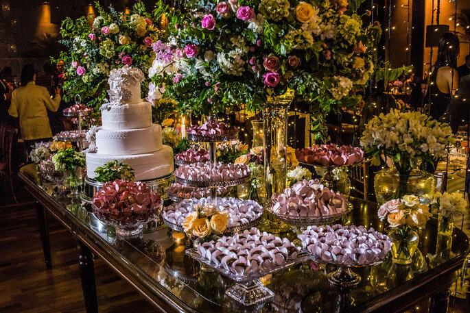 Mazzi Assessoria. Foto da mesa decorada com flores, doces e bolo de casamento