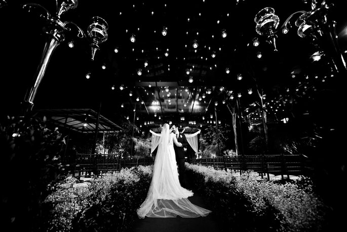 noivos embaixo de castiçais de vela em casamento no jardim