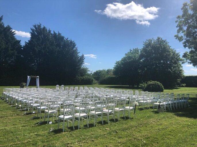 Jardins avec des chaises blanches disposées en rang et une arche, propice à la célébration d'une cérémonie laïque