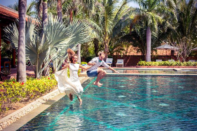 Deux mariés sautent dans une piscine