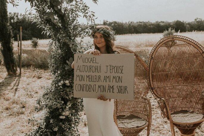 Ma Petite Cérémonie - une mariée dans un décor bohème qui lui correspond, avec une arche de feuilles, deux fauteuils en osier et un champ en toile de fond