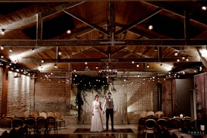 noivos de mãos dadas numa sala com teto de madeira estilo rústico chic