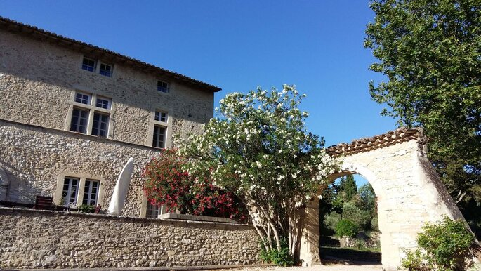 Une façade en pierres, un porche et de jolis arbres fleuris