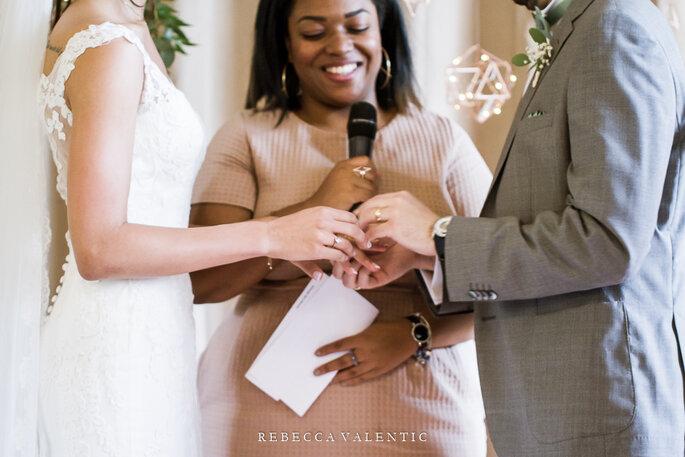 Fabiola et un couple de mariés qui s'échangent leurs alliances pendant la cérémonie laïque.