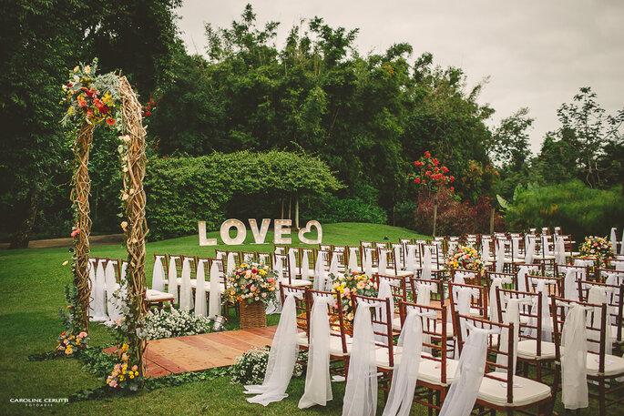 Cerimônia de casamento no campo, com letreiro iluminado LOVE