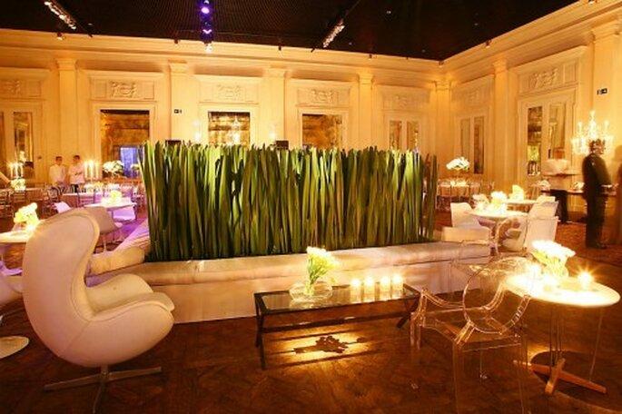 Área lounge con medio muro vegetal y sillas de acrilico