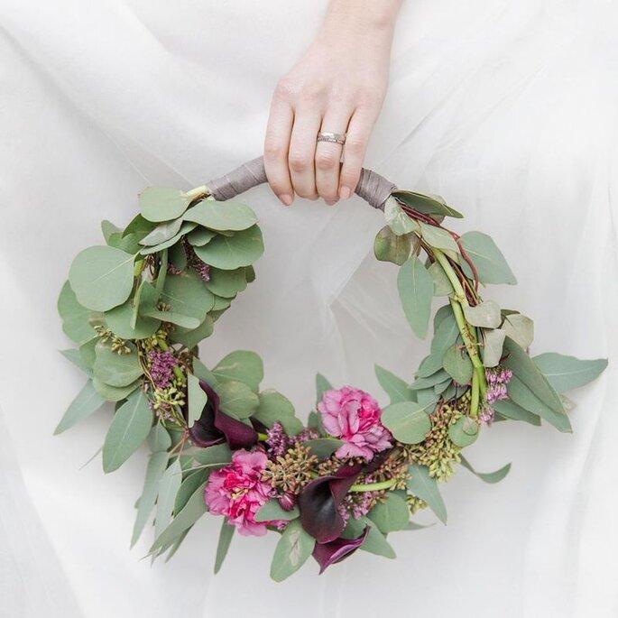 weibliche Hand mit Ehering hält Blumenkranz