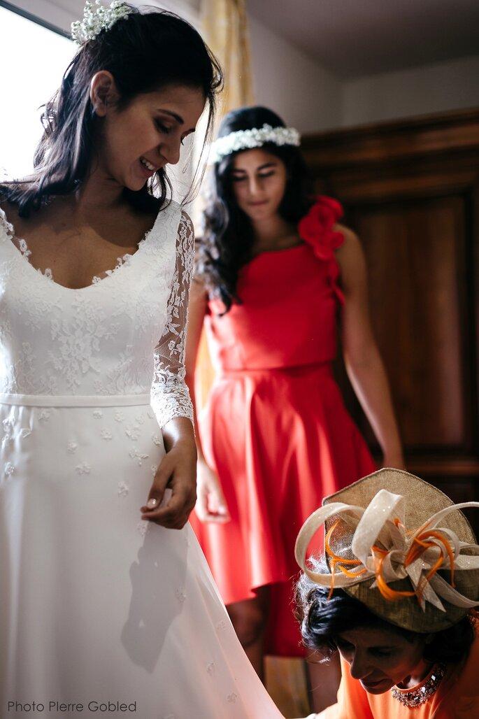 Laurent Kapelski - Une mariée avec sa maman qui réajuste sa robe et sa demoiselle d'honneur en arrière plan qui porte une robe rouge et une couronne de fleurs blanche