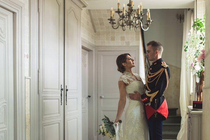 Un couple de mariés élégant enlacé à l'intérieur d'une belle demeure