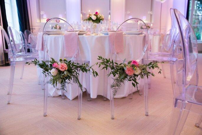 Une table dressée pour un mariage, épurée, avec des fleurs accrochées sur des chaises transparentes et une lumière rose tamisée