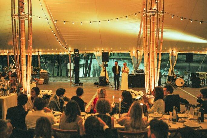 Une grande fête de mariage a lieu sous un chapiteau, en plein air
