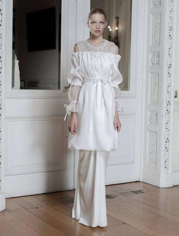 Vestido de novia con cuello ilusión, apliques de pedrería, frunces y mangas con transparencias - Foto Sophia Kokosalaki
