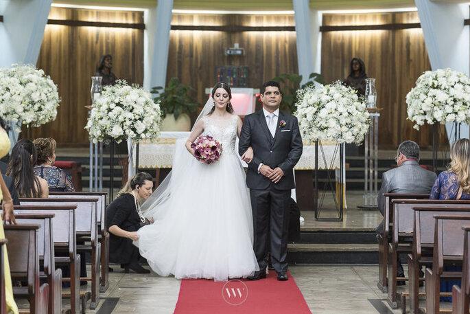 Cerimonialista ajeita o vestido para a saída da igreja