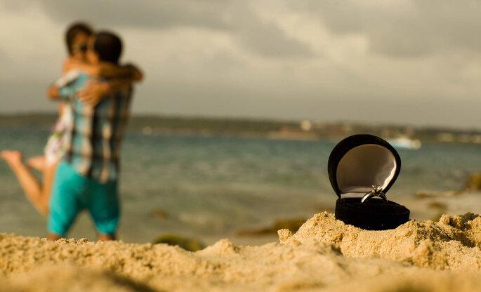 Primer plano anillo de matrimonio en la arena y de fondo pareja celebrando