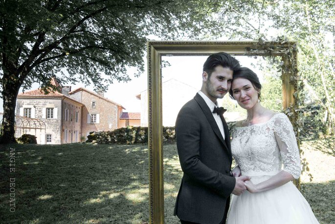 Un couple de mariés prend la pose devant son lieu de réception en Gironde.