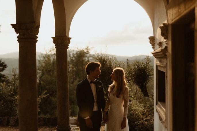 Couple de marié au coucher du soleil qui se regarde dans les yeux