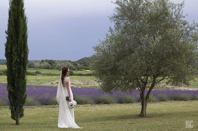 Alexandre Moulard : Une mariée pose devant un champ de lavande, à côté d'un olivier, un bouquet de pivoines à la main