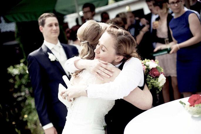 Die Traurednerin umarmt eine ihrer Bräute.