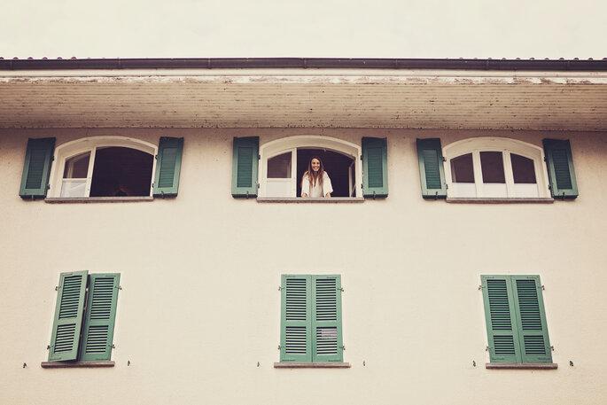 Hochzeitsfotografie.Braut schaut aus Fenster der Hochzeitslocation