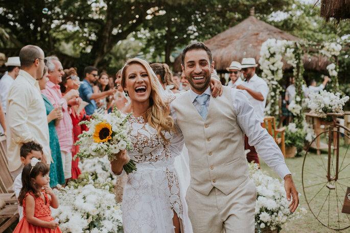 Noivos abraçados no final da cerimônia de casamento. Noiva com buquê de Girassol