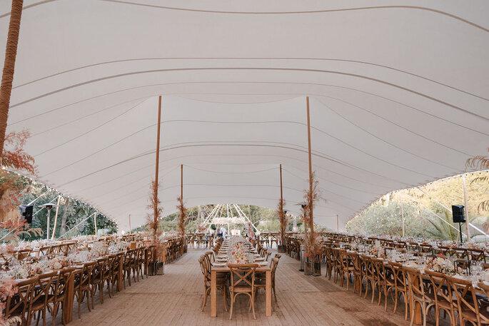 Tentes de location blanches dressées dans un parc avec des tables et chaises en bois décorées pour un mariage style bohème