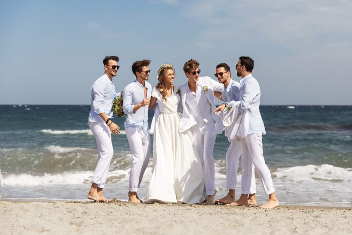 Un couple de mariés entouré par ses invités sur une plage.