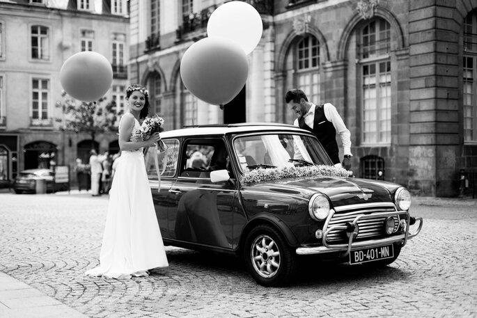 Deux mariés et leur voiture de location décorée pour leur mariage