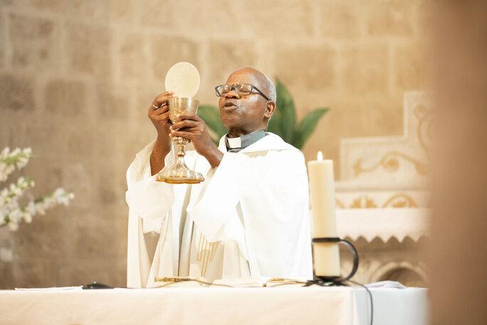 Un prêtre avec son ostie à la main pour officier un mariage à l'église