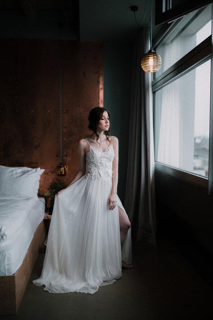 Die Braut trägt das Brautkleid und schaut aus dem Fenster.