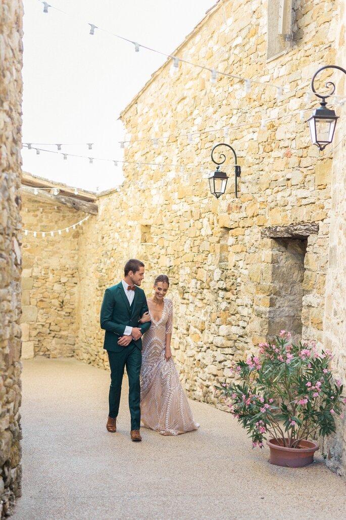 Des mariés heureux marchent ensemble dans une ruelle aux murs de pierre
